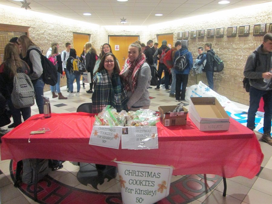 Two helpers selling treats during the bake sale.