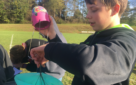Jeremiah Bloom fixes the parachute on his rocket after a failed attempt.