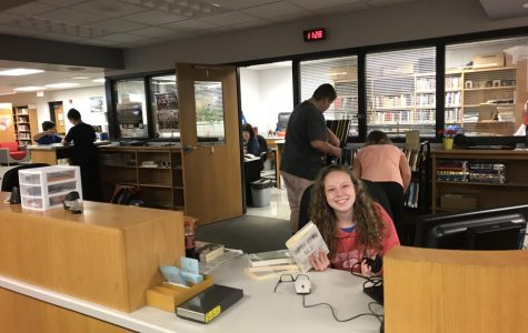 Hannah Columbus checking out books at the school library.