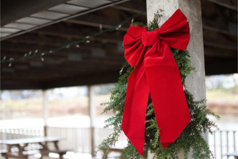 A wreath and bow placed on the wooden beams of a picnic area near the Susquehanna River downtown with string lights behind them, not yet illuminated.