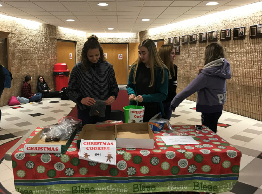 Cassie Hipps and Emma Powell help sell baked good for the Bake Sale.