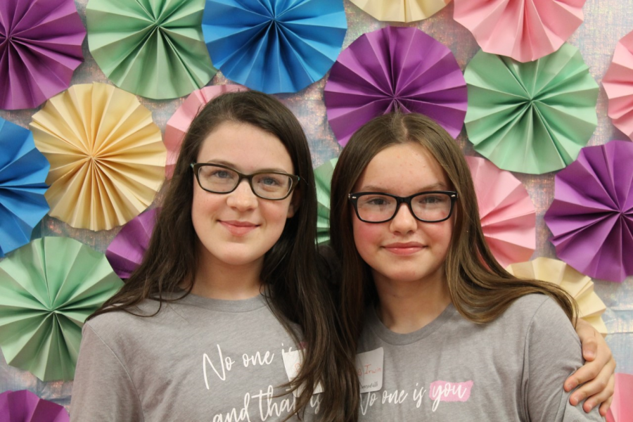 Two students pose in front of a paper flower backdrop for a picture.