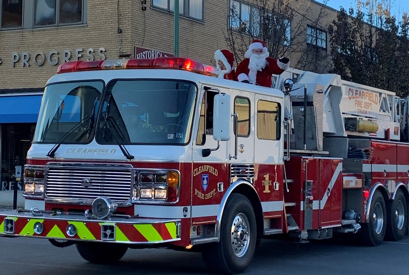 Mr. and Mrs. Claus come to town riding on a fire truck.