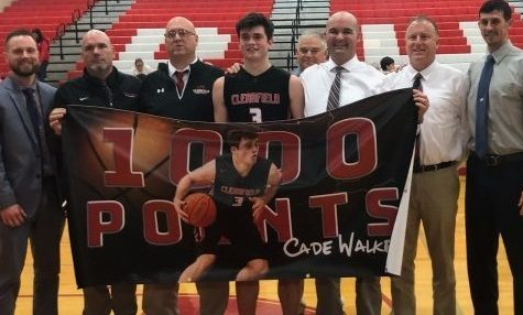 Cade Walker, center, and coaches celebrate Cade's 1,000-point record.