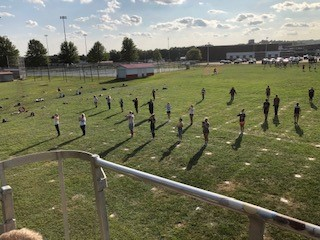 Marching band practicing their half-time show. performance