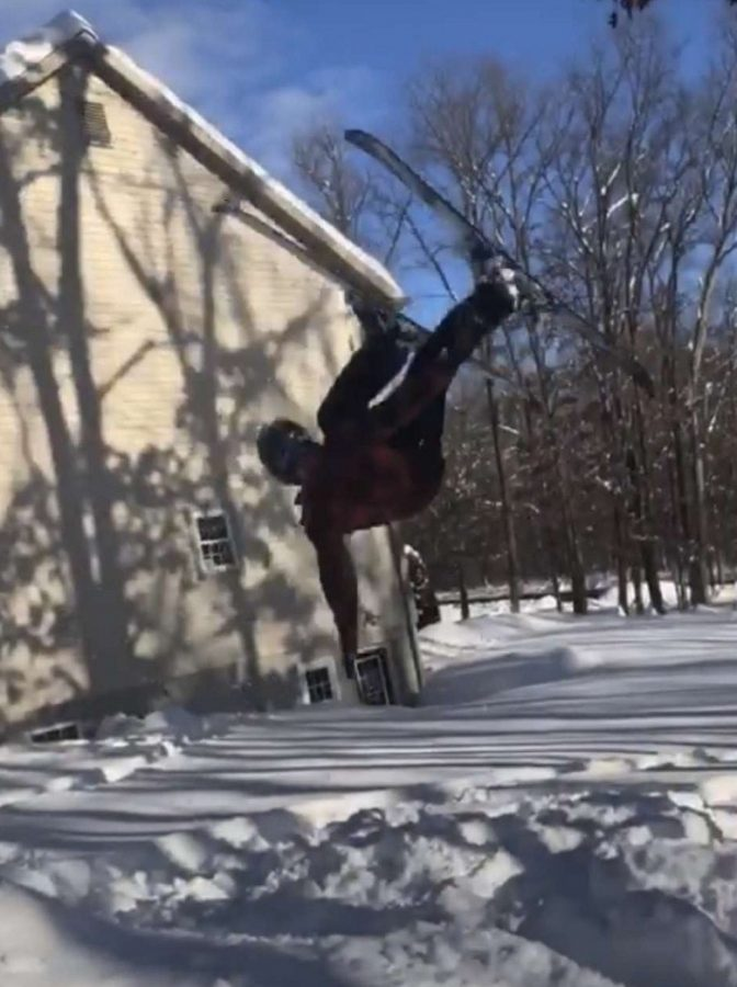 Justin Hand goes flying during a snow day with Haden Allison.