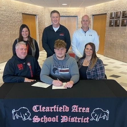 Zane Inguangiato, seated at center, poses with his parents as the following look on, standing from left: Principal Mrs. Prestash, Football Coach Mr. Janocko, and Athletic Director Mr. Gearheart.